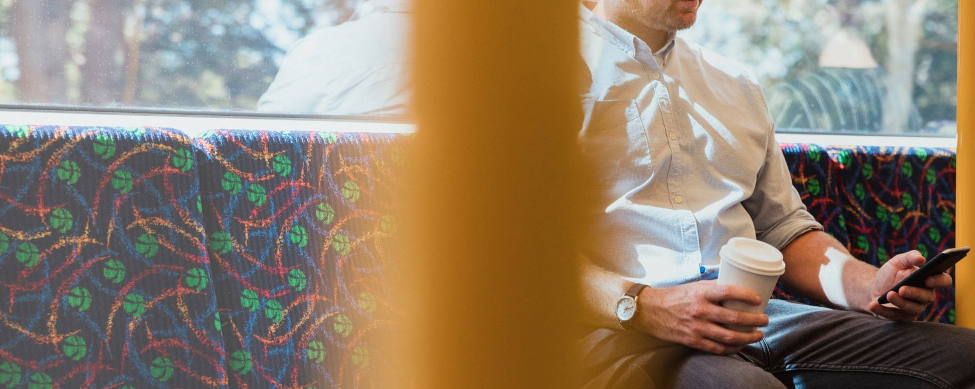 A male looking at his phone on a train