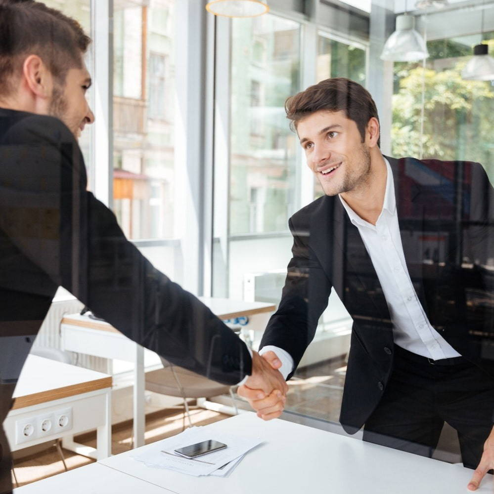 A young male professional shaking hands with an interviewer